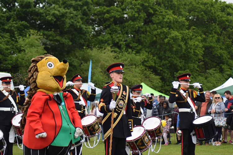 Sandhurst and District Corps of Drums performing in the Arena with show mascot Spike the Hedgehog